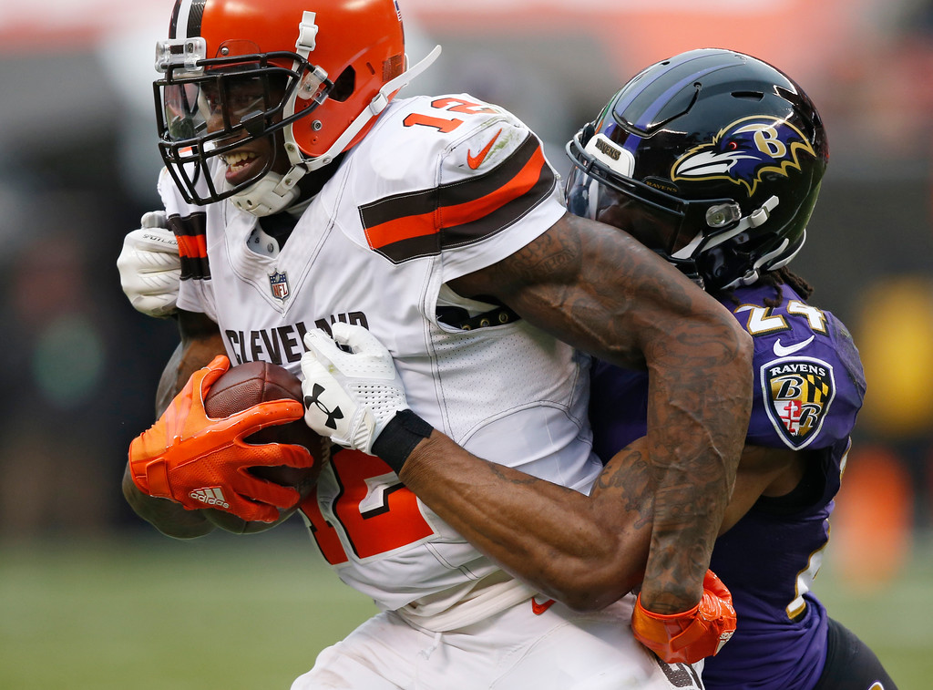 . Baltimore Ravens cornerback Brandon Carr (24) tackles Cleveland Browns wide receiver Josh Gordon (12) during the second half of an NFL football game, Sunday, Dec. 17, 2017, in Cleveland. (AP Photo/Ron Schwane)