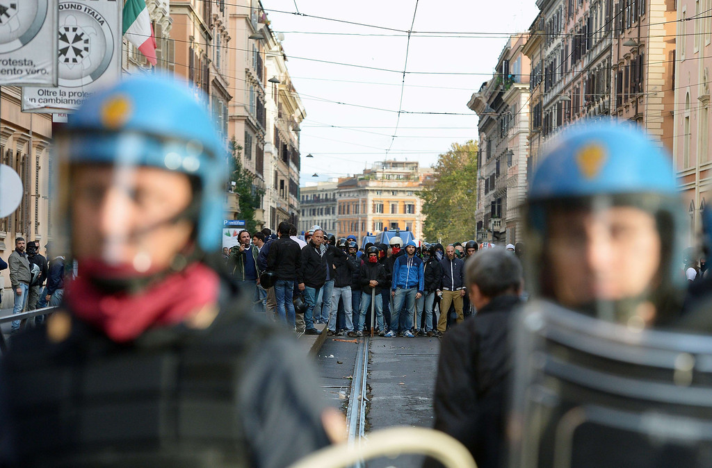 . A group of men from the CasaPound (a social center of fascist inspiration) holding batons faces anti-riot policemen as thousands of people march during an anti-austerity protest on October 19, 2013 in Rome. Between 3,000 and 4,000 police officers have been deployed, Italian media reports said, and protest organizers say they expect more than 20,000 to join. ALBERTO PIZZOLI/AFP/Getty Images