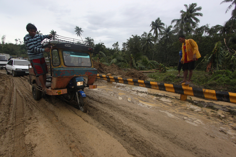 Description of . Commuters maneuver their vehicles through a muddy portion of a highway after Typhoon Bopha made a landfall in Compostela Valley in southeastern Philippines Tuesday Dec. 4, 2012. A Philippine governor says at least 33 villagers and soldiers have drowned when torrents of water dumped by the powerful typhoon rushed down a mountain, engulfing the victims and bringing the death toll from the storm to about 40. (AP Photo/Karlos Manlupig)