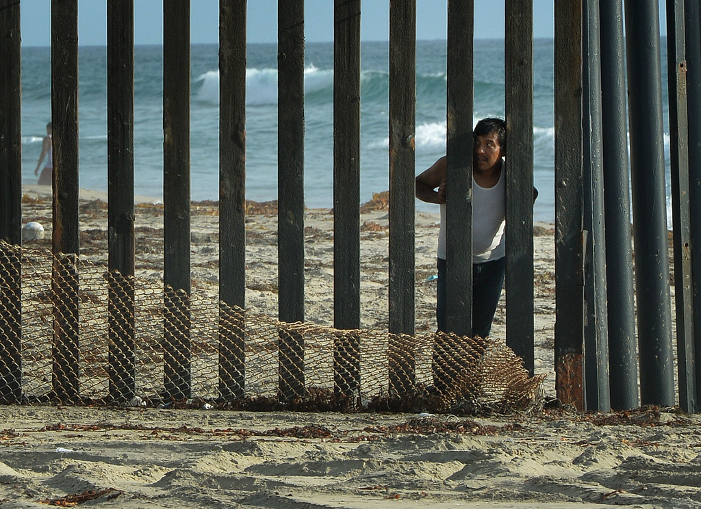 . A man looks out towards the US from the Mexican side of the border fence that divides the two countries in San Diego on August 20, 2014.  At least 57,000 unaccompanied children, most from Honduras, Guatemala and El Salvador, have crossed the border into the United States illegally since October, triggering a migration crisis that has sent US border and immigration authorities into a frenzy.                  AFP PHOTO/Mark RALSTON/AFP/Getty Images