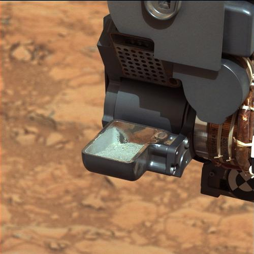 . This March 2013 image released by NASA shows the Curiosity rover holding a scoop of powdered rock on Mars before analyzing its chemical makeup. (AP Photo/NASA)