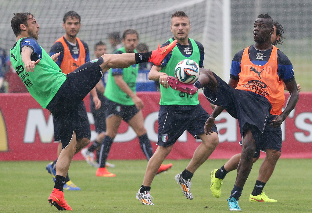 . Italy\'s Mario Balotelli, right, challenges teammate Claudio Marchisio, for the ball, during a training session in the rain, in Mangaratiba, Brazil, Tuesday, June 10, 2014. Italy will play in group D of the Brazil 2014 soccer World Cup. (AP Photo/Antonio Calanni)