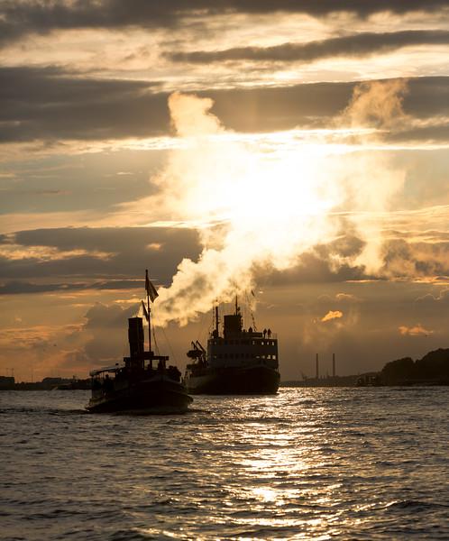 Dampfschiffe auf der Elbe im Gegenlicht in Hamburg
