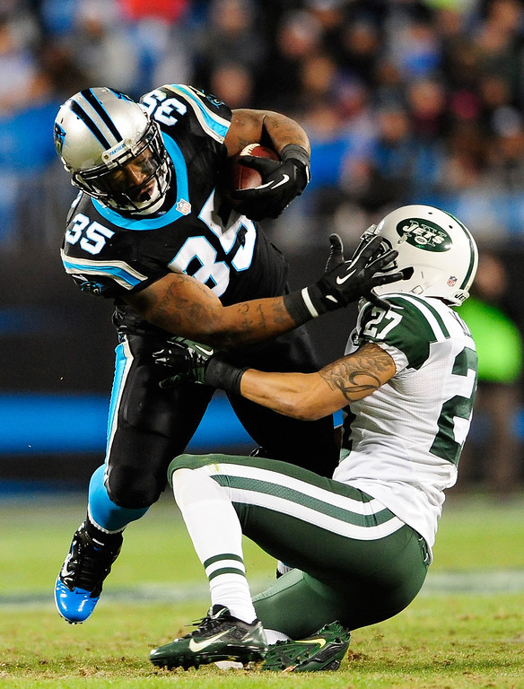 . Mike Tolbert #35 of the Carolina Panthers fights through the tackle of Dee Milliner #27 of the New York Jets during play at Bank of America Stadium on December 15, 2013 in Charlotte, North Carolina. The Panthers won 30-20.  (Photo by Grant Halverson/Getty Images)