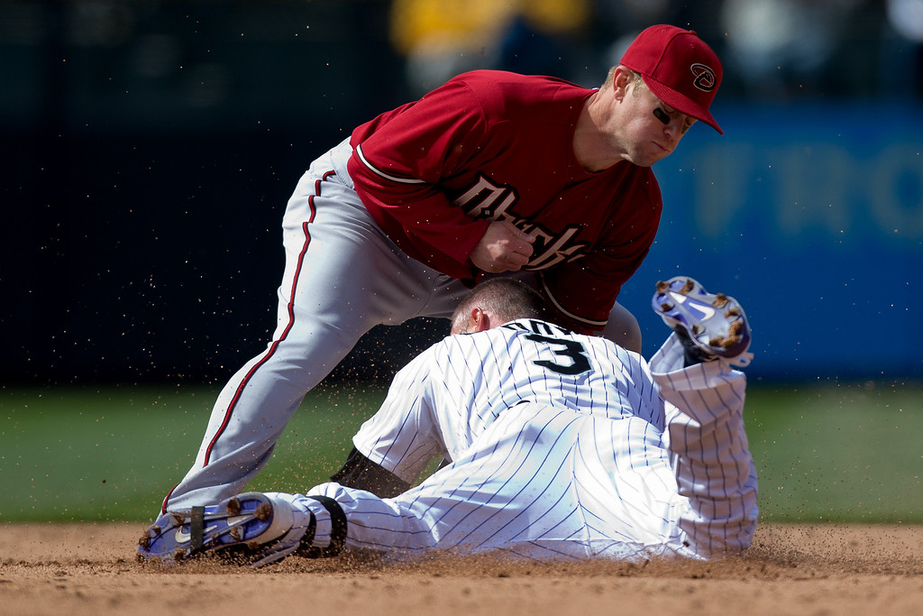 . Michael Cuddyer #3 of the Colorado Rockies collides with shortstop Chris Owings #16 of the Arizona Diamondbacks after sliding in for a double during the fourth inning at Coors Field on April 6, 2014 in Denver, Colorado. The Diamondbacks defeated the Rockies 5-3. (Photo by Justin Edmonds/Getty Images)