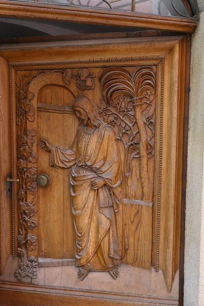 An ancient carved door of Jesus in the vineyard.