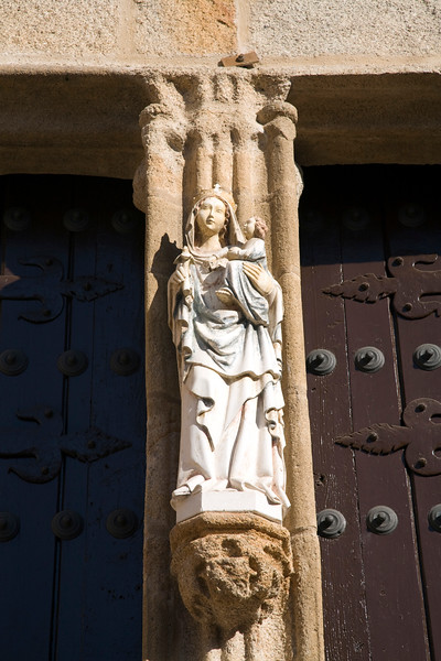 Gothic sculpture of the Virgin Mary on the mullion of the cathedral entrance, Caceres, Spain