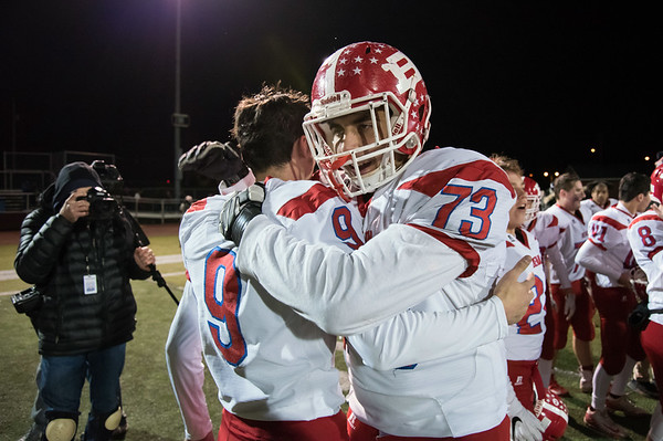 12/03/18 Wesley Bunnell | Staff Berlin football defeated Sheehan on Monday evening at Sheehan High School to advance to the class M championship game vs St. Joe's. Kevin Dunn (9) hugs Paul D'Amore (73) after their victory.