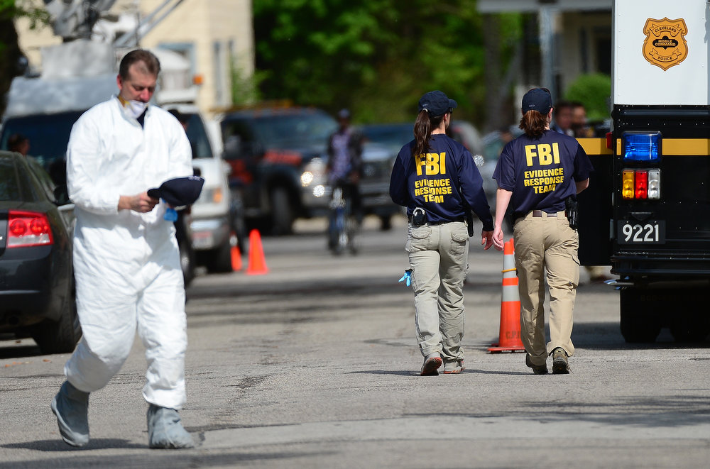 . FBI forensic personnel walk near the house where three women were held captive for a decade on May 7, 2013 in Cleveland, Ohio.  Ariel Castro, a 52-year-old former school bus driver, has been arrested in connection with the kidnapping of three women found safe in a home after missing for a decade, authorities said. There were more questions than answers the day after the stunning turn of events that began with a frantic arm sticking out of a screen door, a woman screaming for help, and a neighbor kicking in the door to free her in a working-class neighborhood of the city in the American heartland.  EMMANUEL DUNAND/AFP/Getty Images