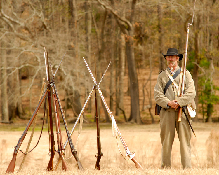 A single gentleman stands with his weapon at the ready near two stacks of arms on the battlefield. The Skirmish at Gamble's Hotel happened on March 5, 1885 when 500 federal soldiers, under the command of Reuben Williams of the 12th Indiana Infantry, marched into Florence to destroy the railroad depot but were met by Confederate soldiers backed up with 400 militia. The reenactment, held by the 23rd South Carolina Infantry, was held at the Rankin Plantation in Florence, South Carolina on Saturday, March 5, 2011. Photo Copyright 2011 Jason Barnette