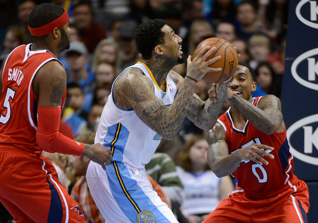 . Wilson Chandler (21) of the Denver Nuggets gets hit on the wrist by Jeff Teague (0) of the Atlanta Hawks during the third quarter March 4,  2013 at Pepsi Center. The Denver Nuggets defeated the Atlanta Hawks, 104-88. (Photo By John Leyba/The Denver Post)