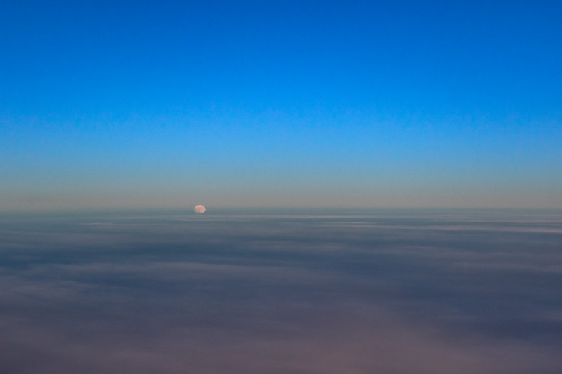 Looking out a plane window and seeing the full moon rising above the clouds