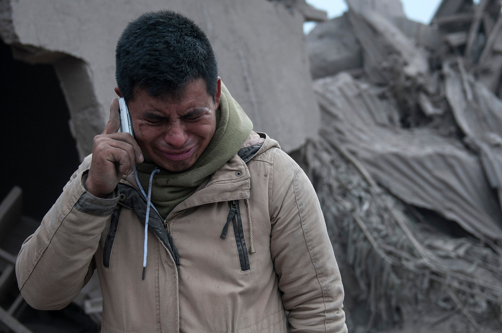 ". Boris Rodriguez, 24, who is searching for his wife, cries after seeing the condition of his neighborhood, destroyed by the erupting Volcan de Fuego, or ""Volcano of Fire,\"" in Escuintla, Guatemala, Monday, June 4, 2018. The volcano exploded Sunday, sending ash high into the sky and lava flows cascading into rural hamlets on the mountain\'s slopes. (AP Photo/Oliver de Ros)"