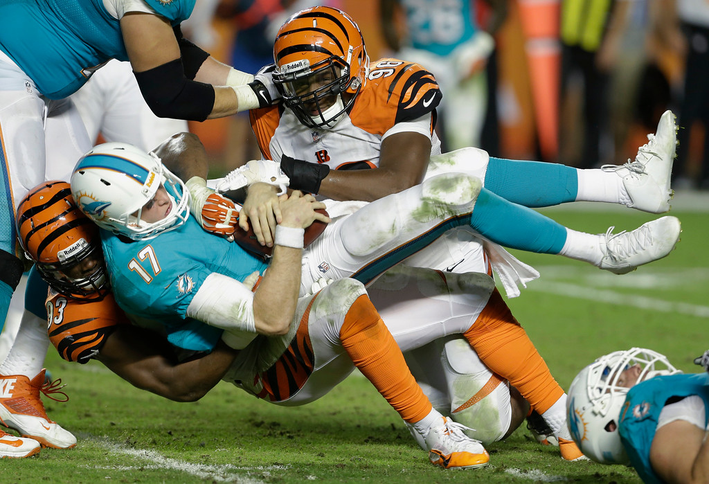 . Miami Dolphins quarterback Ryan Tannehill (17) is sacked by Cincinnati Bengals defensive ends Carlos Dunlap (96) and Michael Johnson (93) during the second half of an NFL football game, Thursday, Oct. 31, 2013, in Miami Gardens, Fla. (AP Photo/Lynne Sladky)
