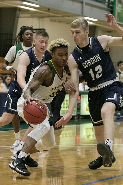 Fitchburg State University mens basketball played Gordon College on thursday night at FSU's Recreation Center. CG's #12 Garrett Sattazahn tries to stop FSU's #34 Anthony Diaz. SENTINEL & ENTERPRISE/JOHN LOVE