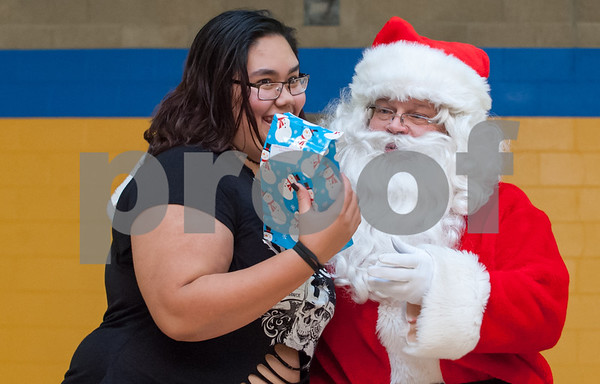 12/12/17 Wesley Bunnell | Staff New Britain OIC held their annual Christmas Party on Tuesday afternoon featuring food, music and presents for all members. Ashia Bravo, L, smiles as she receives a present from Executive Director of the New Britain Downtown District Gerry Amodio dressed as Santa.
