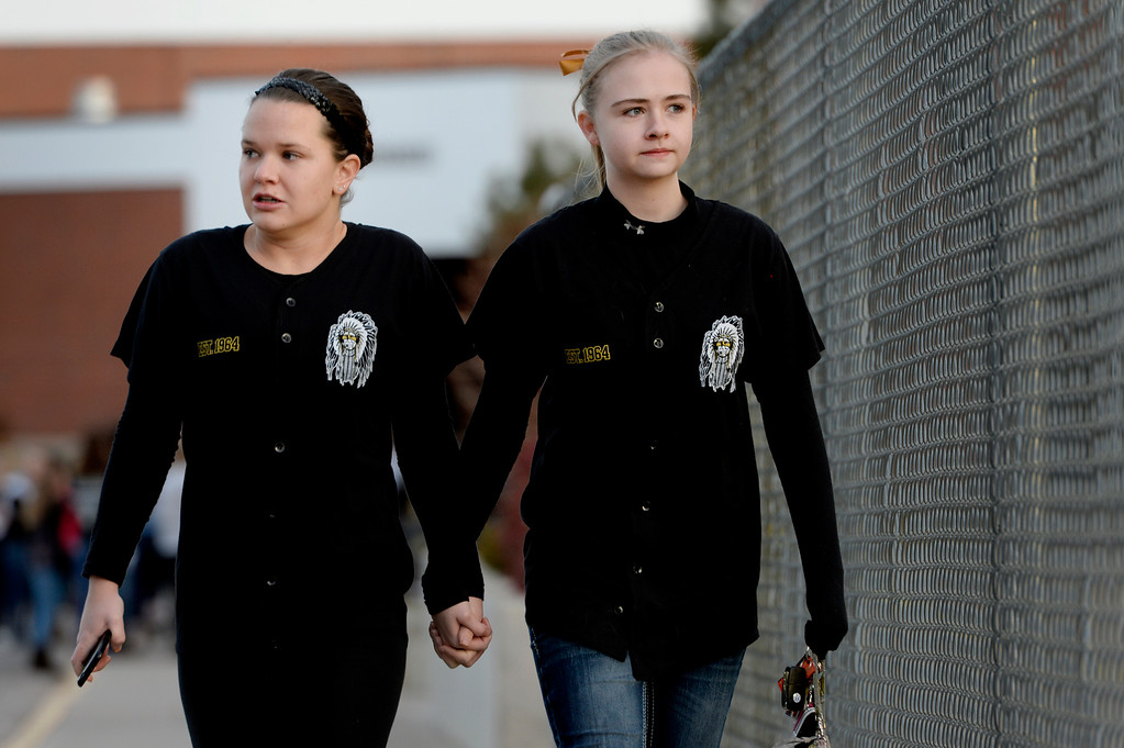 """. Seniors Amanda Bridges, right, and Melissa Tombaugh make their way to the tribute area before visiting Arapahoe High School in Centennial, CO December 19, 2013. Seniors and Juniors returned to the school for two hour periods Thursday, Sophomores and Freshmen will return on Friday. Melissa said, \""""it\'s rough, I\'m a little nervous.\"""" The victim from Friday�s shooting at Arapahoe High School, Claire Davis, 17, remains in critical condition. She was shot on Friday when classmate Karl Pierson opened fire in the school. The gunman died from a self-inflicted gunshot wound. (Photo By Craig F. Walker / The Denver Post)"""