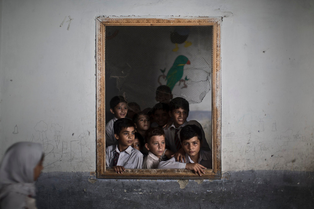 . Pakistani schoolboys look out the window of their classroom at other classmates chanting prayers to commemorate the anniversary of Malala\'s shooting by Taliban, at a school in Rawalpindi, Pakistan, Wednesday, Oct. 9, 2013.  One year after a Taliban bullet tried to silence Malala Yousufzai\'s demand for education, she has published a book and is a contender for the Nobel Peace Prize. But the militants threaten to kill her should she dare return home from Britain to Pakistan, and the principal at her old school says that as Malala\'s fame has grown, so has fear in her classrooms. (AP Photo/Muhammed Muheisen)