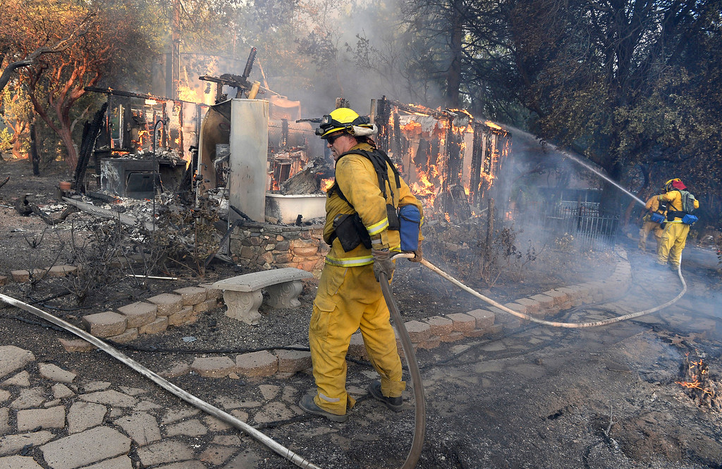 . In this Sunday, Sept. 14, 2014 photo, firefighters work a structure fire in Oakhurst, Calif., as two raging wildfires in the state forced hundreds of people to evacuate their homes.  (AP Photo/The Fresno Bee, Mark Crosse) L