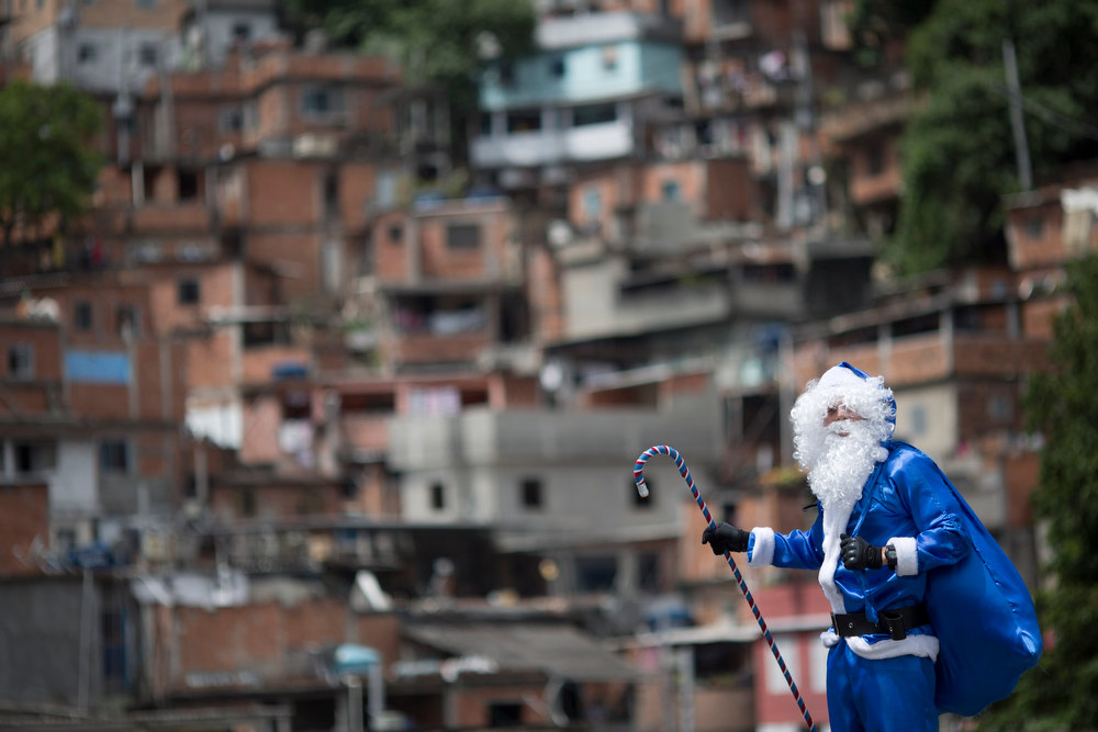 Description of . A police officer dressed in a blue Santa Claus costume holds a sack and cane in the Macacos slum after arriving by police helicopter in Rio de Janeiro, Brazil, Thursday, Dec. 20, 2012. The Pacifying Police Unit, or UPP, organized for Santa to visit the pacified slum to hand out Christmas gifts to young residents. (AP Photo/Felipe Dana)