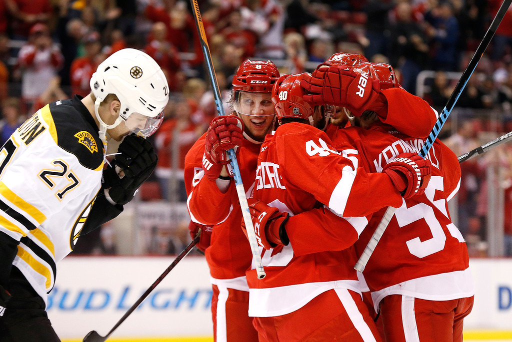 . Detroit Red Wings left wing Justin Abdelkader, left, celebrates his goal as Boston Bruins Dougie Hamilton (27) skates by in the second period of an NHL hockey game in Detroit Thursday, Oct. 9, 2014. (AP Photo/Paul Sancya)