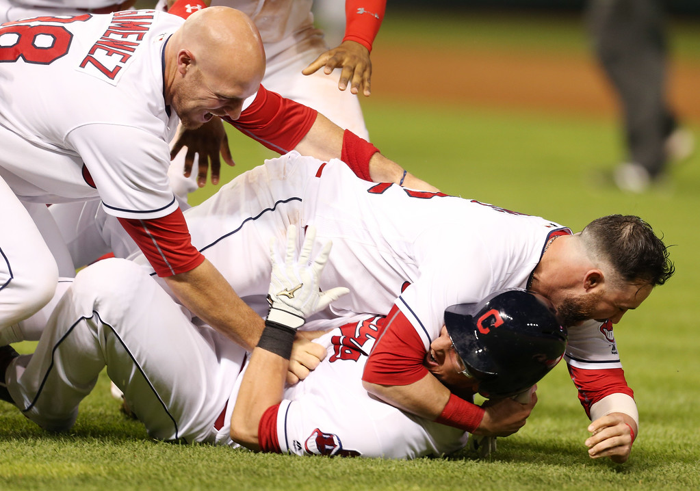 . Cleveland Indians\' Yan Gomes, bottom, is tackled by Jason Kipnis and Chris Gimenez, left, after hitting a single to score the winning run against the Texas Rangers during the 11thinning of a baseball game Wednesday, June 1, 2016, in Cleveland. The Indians won 5-4. (AP Photo/Ron Schwane)