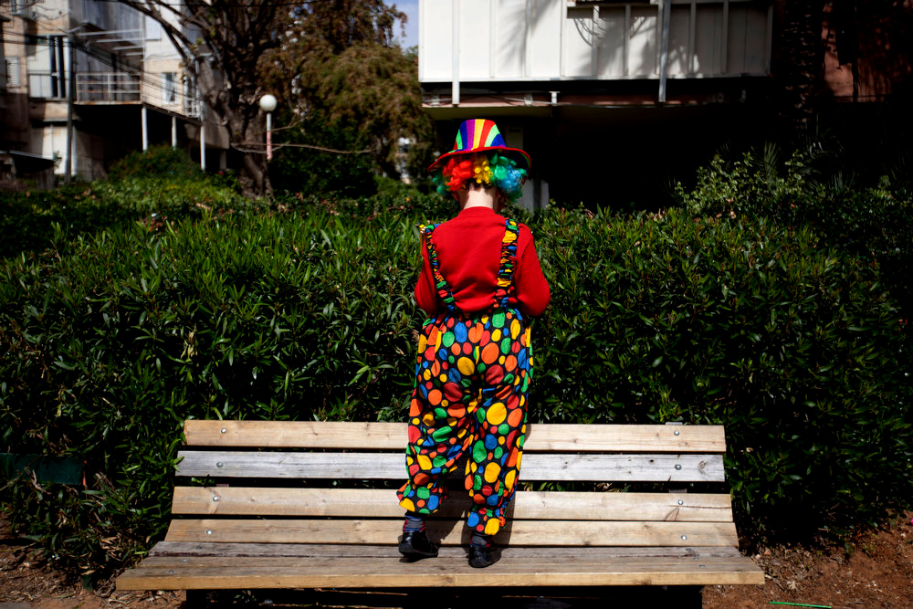 Description of . An Ultra Orthodox Jewish boy dressed up as a clown stands on a bench outside a synagogue during the Purim festival in the ultra-Orthodox town of Bnei Brak, Israel, Sunday, Feb. 24, 2013. The Jewish holiday of Purim commemorates the Jews\' salvation from genocide in ancient Persia, as recounted in the Book of Esther which is read in synagogues. Other customs include: sending food parcels and giving charity, dressing up in masks and costumes, eating a festive meal, and public celebration. (AP Photo/Ariel Schalit)
