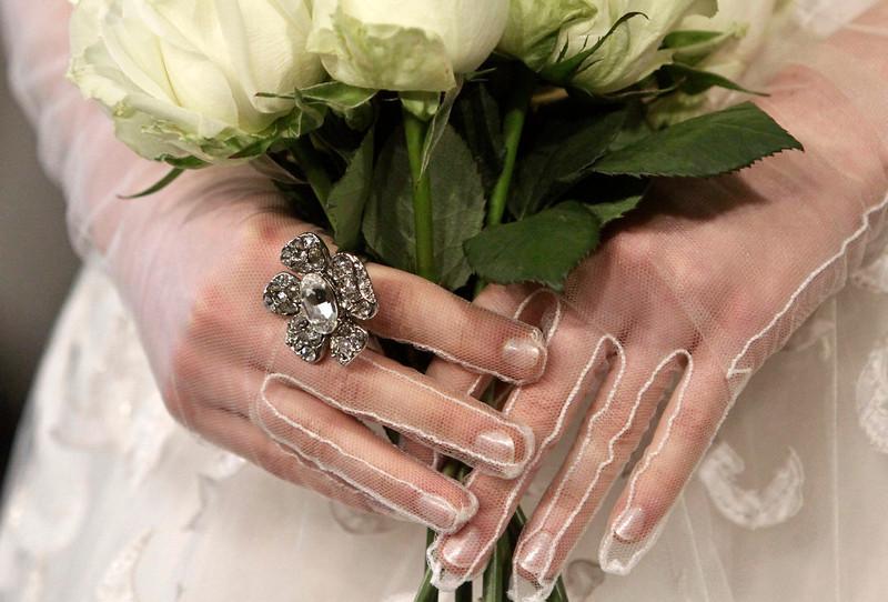 . A model presents a bridal fashion creation from the Oscar de la Renta collection, in New York, Monday, April 22, 2013. (AP Photo/Bebeto Matthews)