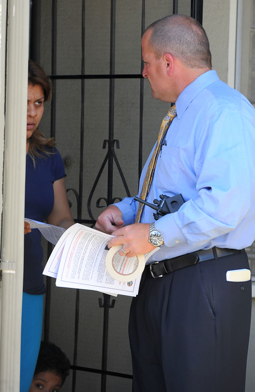 """. Long Beach police detective Don Collier hands out fliers to people in a neighborhood surrounding 7th Street and Orange Avenue in Long Beach, CA on Tuesday, May 13, 2014. The LBPD is looking for witnesses or anyone with knowledge of the March 24 shooting at the Cerritos Mini Market which left owner Felix Avela in critical condition after being shot during a robbery. The suspect is described as a black male in his late teens or early 20\'s with an average build and wearing a black hoodie sweatshirt with the word \""""Cali\"""" on the front. Anyone with info is asked to call LBPD at 562-570-7464 or 800-222-TIPS. (Photo by Scott Varley, Daily Breeze)"""