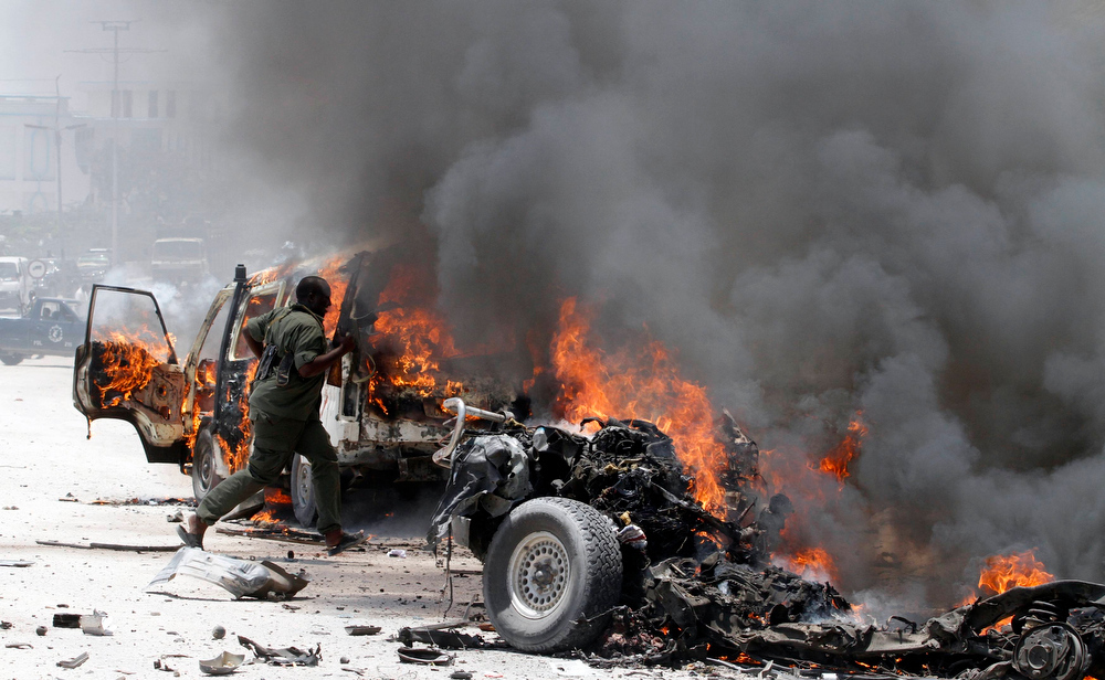 . A policeman runs through burning vehicles at the scene of an explosion near the presidential palace in Somalia\'s capital Mogadishu, March 18, 2013. A car bomb exploded near the presidential palace in the Somali capital Mogadishu on Monday, killing at least 10 people in a blast that appeared to target senior government officials, police said. REUTERS/Feisal Omar