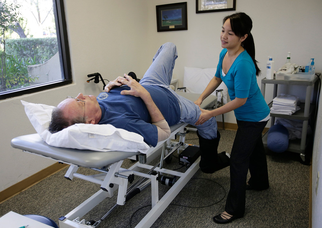 . Lisa Yee, physical therapist, loosens Gary Richards leg during a physical therapy session for a heel problem in Cupertino, Calif. on Thursday, Feb. 28, 2013. Richards  is the Mercury News Roadshow columnist who is calling attention to aging motorists and the issues they face. (Gary Reyes/ Staff)