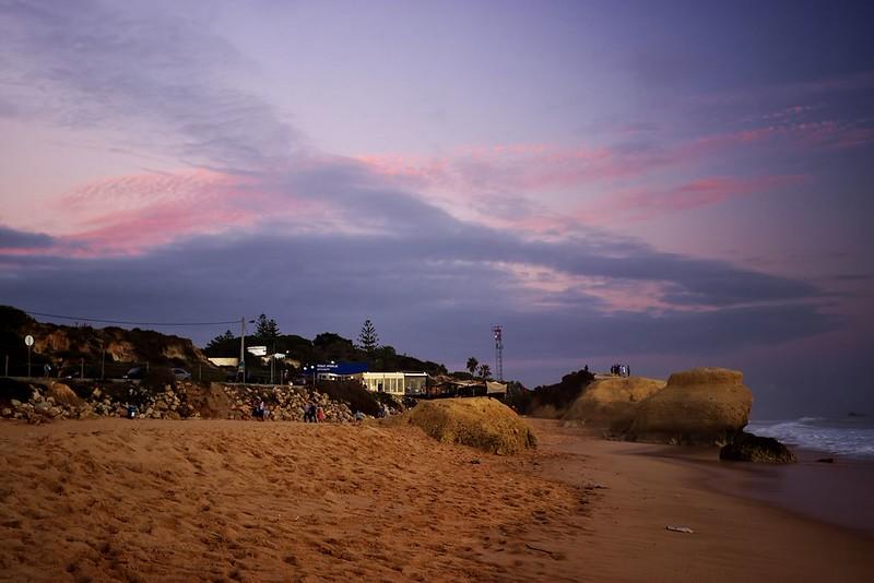 Pláž Galé po západu slunce. Na balvanu vpravo je vidět skupinka fotografů/pozorovatelů, která tam právě kvůli západu slunce vylezla.