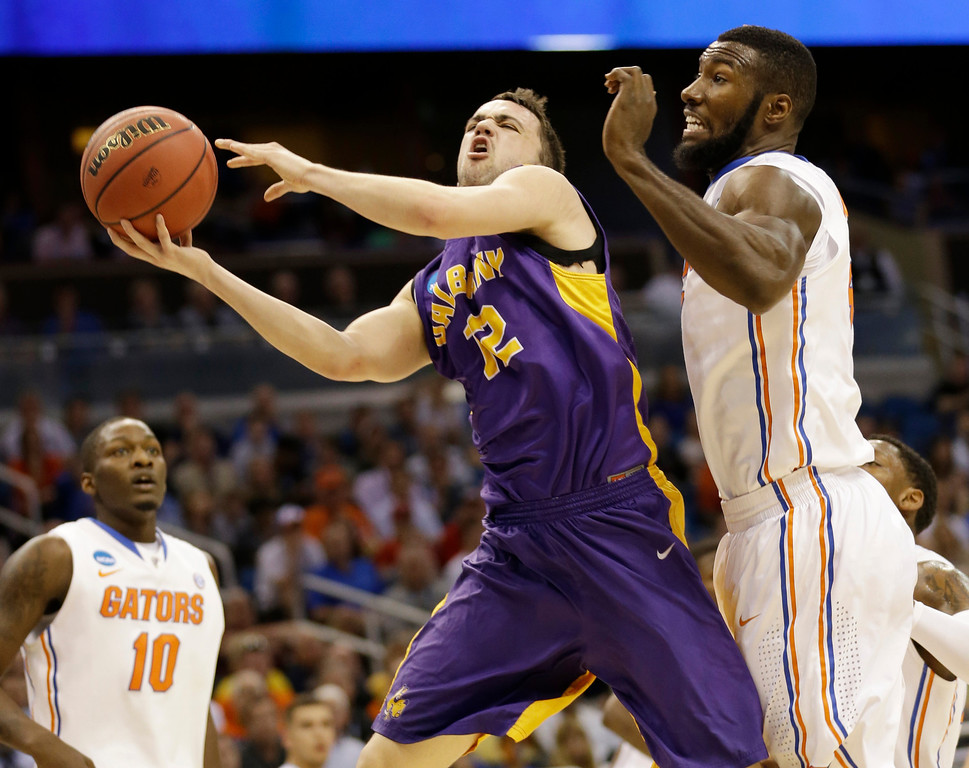 . Albany guard Peter Hooley (12) drives to the basket as Florida center Patric Young (4) defends during the first half of a second-round game in the NCAA college basketball tournament on Thursday, March 20, 2014, in Orlando, Fla. (AP Photo/John Raoux)