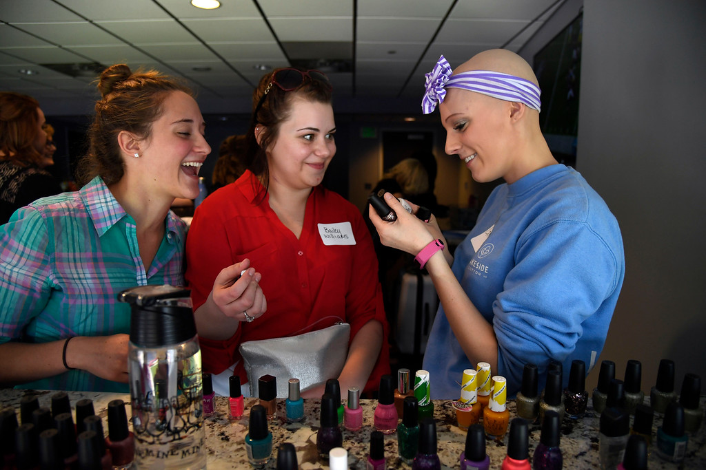 . Karissa Harves, 17, (L) Bailey Williams, 18,  and Grace Jackson, 18, try to decide on nail polish as they get ready for prom. Teens got their makeup, hair and nails done before prom night May 13, 2016 at Sports Authority Field at Mile High. The teen patients had a treat as they got to meet with Denver Broncos quarterback Mark Sanchez who was on hand to greet them. Some of the teens missed their own prom due to illness and just couldn\'t attend. Childrens Hospital hosted the Night of Champions gala. (Photo By John Leyba/The Denver Post)