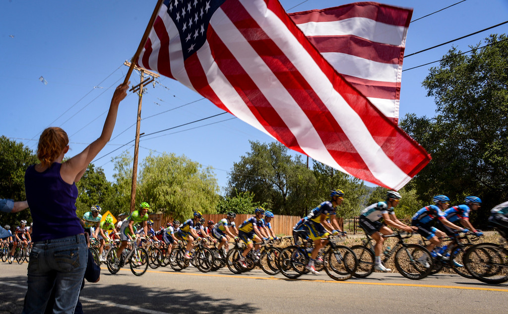 . Holly Swanson waves an american flag as the peleton chases down a 6 rider breakaway on the king of the mountain climb up highway 150 into the Ojai Valley Wednesday.  Stage 4 of the Amgen Tour of California started in Santa Clarita and ended in Santa Barbara.  Photo by David Crane/Staff Photographer