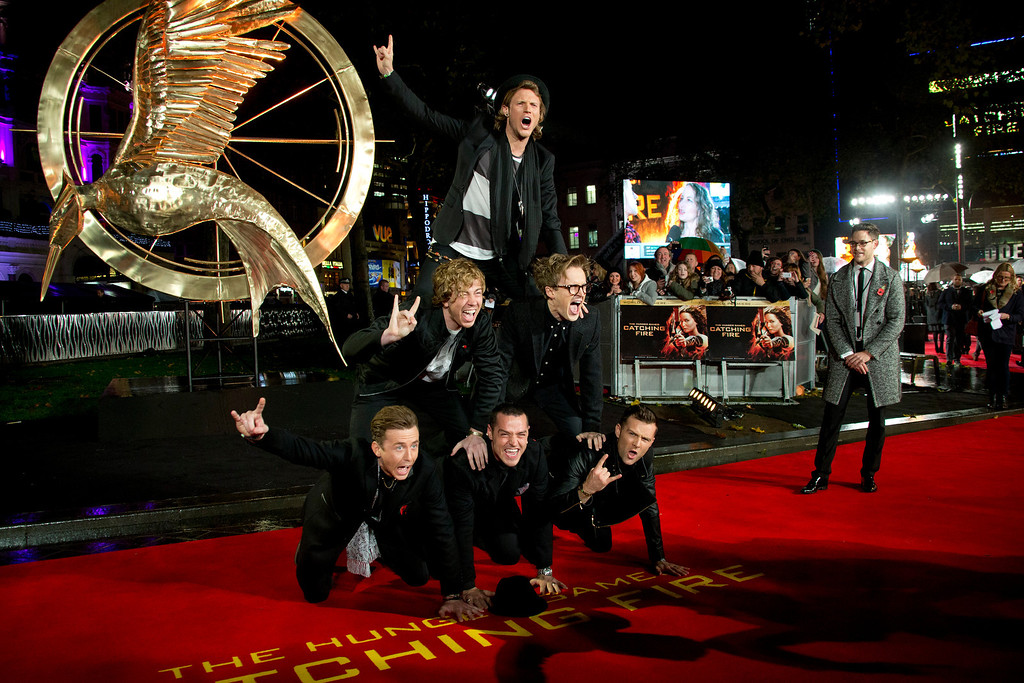 . British boybands McFly and Busted, who have teamed up to form the group McBusted, form a human pyramid on the red carpet for the World Premiere of Hunger Games: Catching Fire, at a central London cinema, Monday, Nov. 11, 2013. (Photo by Joel Ryan/Invision/AP)