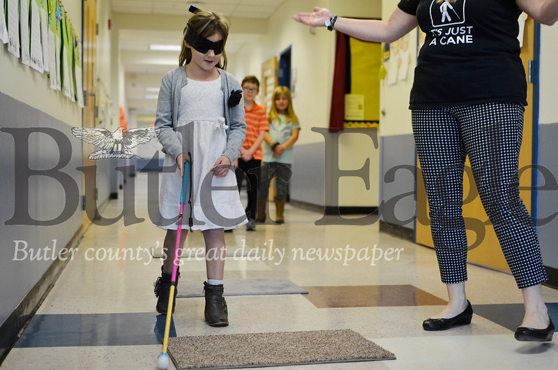 Adalyn White, a legally blind second grade student at McQuistion Elementary School, shows classmates how to use her white cane. Adalyn can see somewhat, so she donned a blindfold like her classmates. Tanner Cole/Butler Eagle