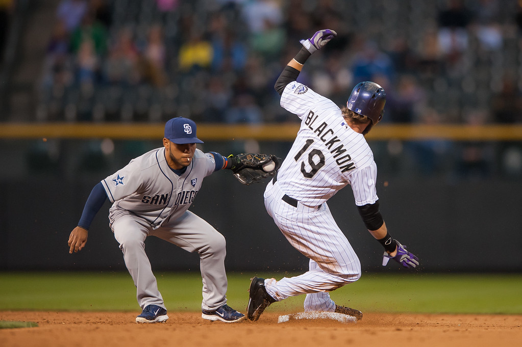 . DENVER, CO - SEPTEMBER 05:  Charlie Blackmon #19 of the Colorado Rockies slides safely into second base with a steal ahead of a tag attempt by Alexi Amarista #5 of the San Diego Padres at Coors Field on September 5, 2014 in Denver, Colorado.  (Photo by Dustin Bradford/Getty Images)