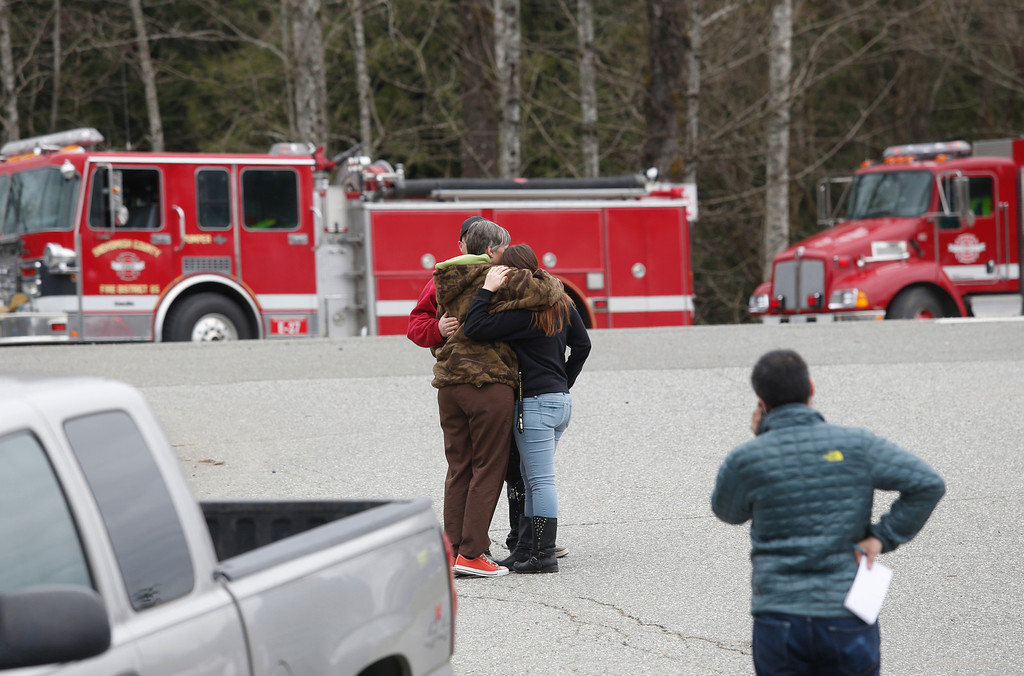 . Neighbors gather at the Oso Fire Department to look for updates about the fatal mudslide that washed over homes and over Highway 530 east of Oso, Wash., Saturday, March 22, 2014. Highway 530 was closed in both directions, and authorities confirmed at least two fatalities by Saturday afternoon. (AP Photo /The Daily Herald, Annie Mulligan)