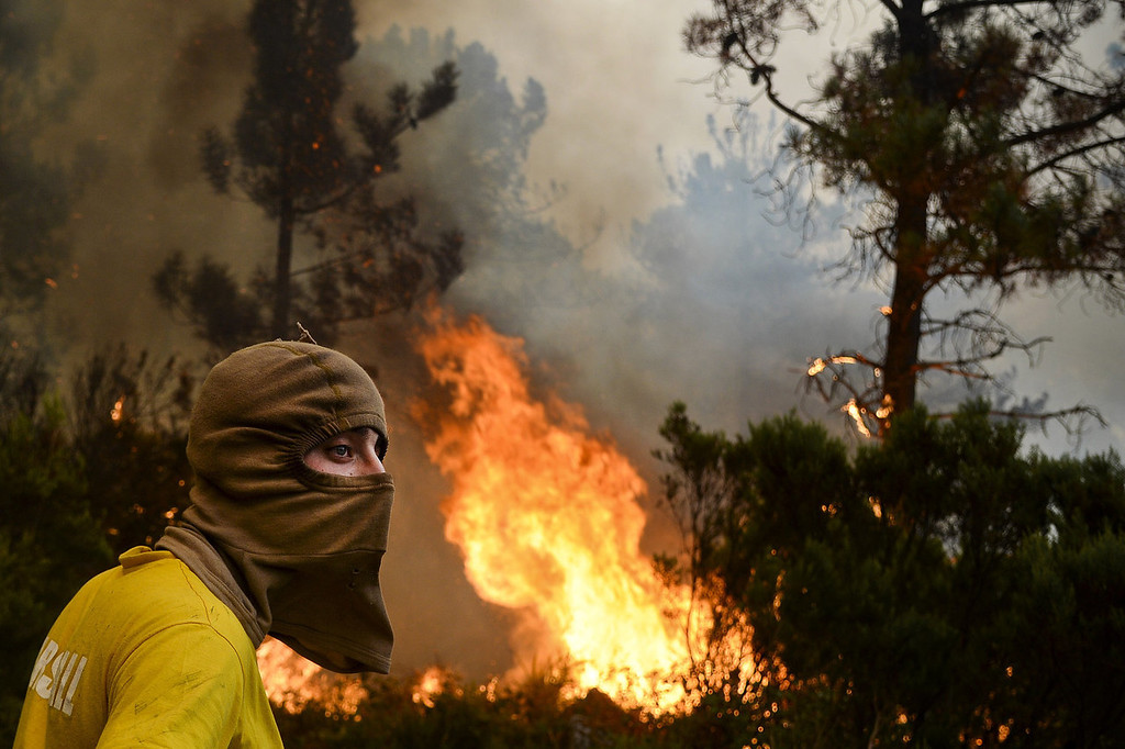 . A local wearing a balaclava stands near a wildfire in Caramulo, central Portugal on August 29, 2013. Five Portuguese mountain villages were evacuated overnight as forest fires intensified in the country\'s north and centre, officials said today. As many as 1,400 firefighters were dispatched Thursday to tackle the blaze in the mountains and another raging further north in the national park of Alvao, where 2,000 hectares (4,900 acres) of pine forest have already been destroyed, according to the local mayor.   PATRICIA DE MELO MOREIRA/AFP/Getty Images