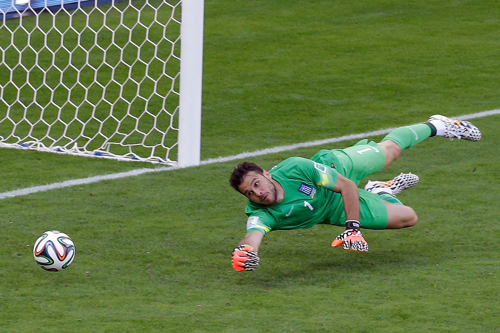 . Greece\'s goalkeeper Orestis Karnezis tries to block a goal by Colombia\'s James Rodriguez (not shown) during the group C World Cup soccer match at the Mineirao Stadium in Belo Horizonte, Brazil, Saturday, June 14, 2014. Colombia won 3-0. (AP Photo/Andrew Medichini)