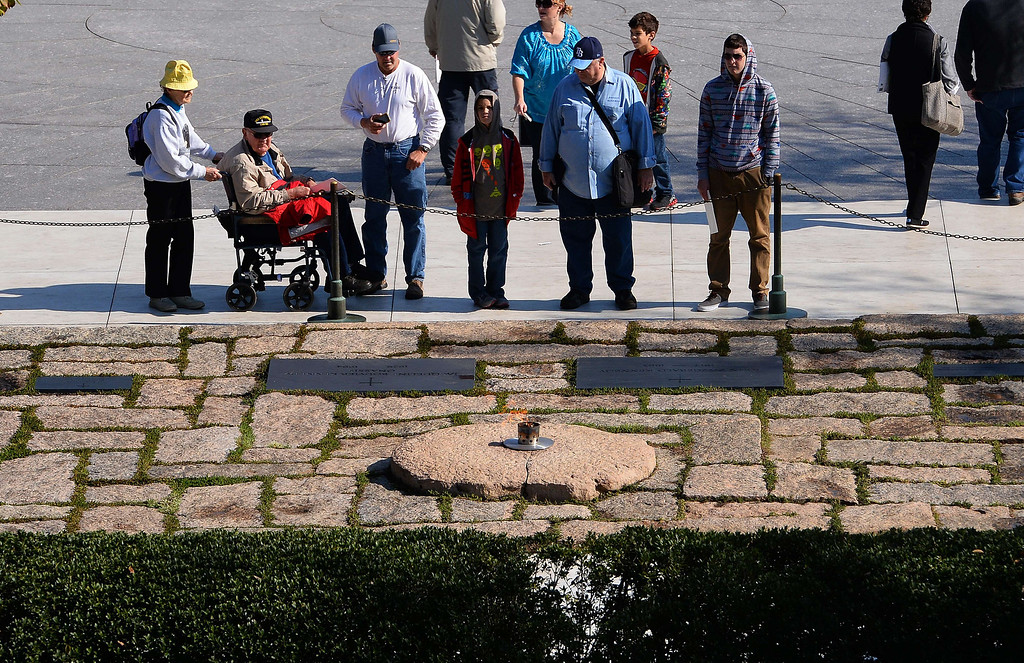 . Tourists visit the gravesite of  former US President John F. Kennedy at Arlington National Cemetery in Arlington, Virginia, on October 29 2013, after a temporary flame was transfered to permanent eternal flame at the site. November 22 marks the 50th anniversary of Kennedy\'s assassination during a visit to Dallas, Texas, in 1963. JEWEL SAMAD/AFP/Getty Images