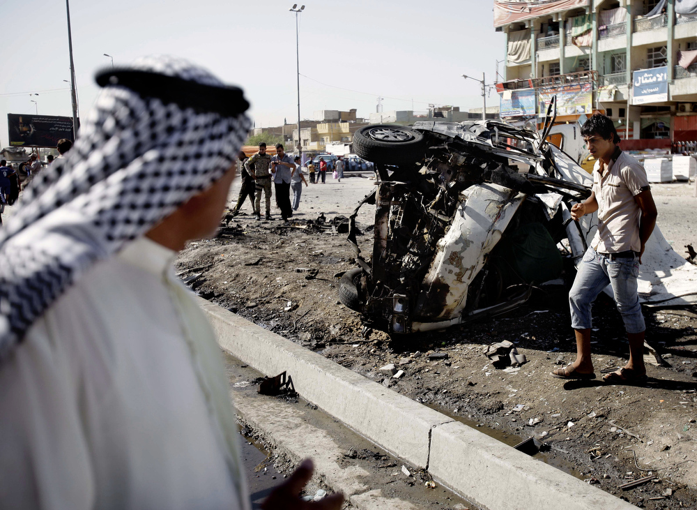 . Iraqis inspect the aftermath of a car bomb attack, in the Shiite enclave of Sadr City, Baghdad, Iraq, Monday, July. 29, 2013. A wave of over a dozen car bombings hit central and southern Iraq during morning rush hour on Monday, officials said, killing scores in the latest coordinated attack by insurgents determined to undermine the government. (AP Photo/Karim Kadim)