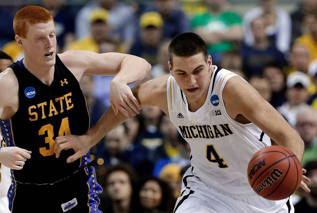 . Michigan forward Mitch McGary (4) steals a pass intended for South Dakota State forward Tony Fiegen (34) in the second half of a second-round game of the NCAA men\'s college basketball tournament in Auburn Hills, Mich., Thursday March 21, 2013. Michigan won 71-56. (AP Photo/Paul Sancya)