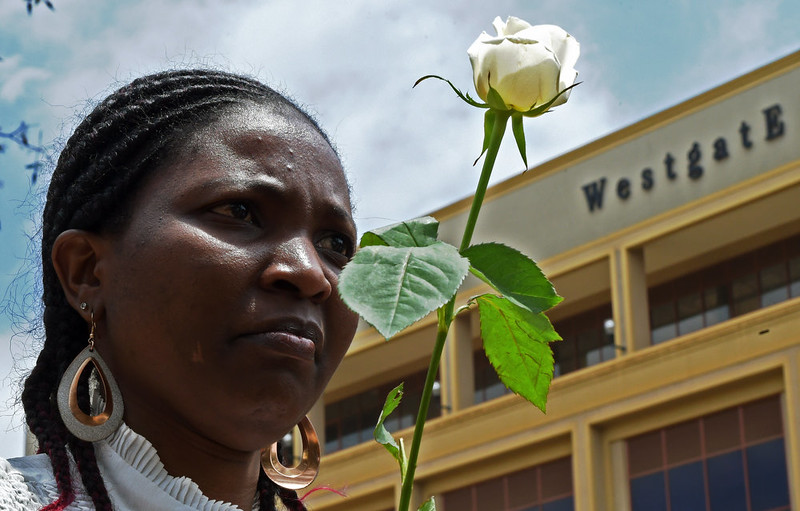 . A woman holds a white rose during a memorial service marking the first anniversary of the Westgate terrorist attack, outside the Westgate mall in Nairobi on September 21, 2014. At least 67 people were killed and scores wounded when a small group of Al-Qaeda affiliated fighters stormed the Westgate mall on September 21 2013. CARL DE SOUZA/AFP/Getty Images