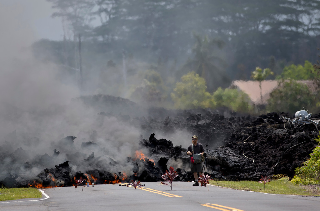 . A man films the lava in the Leilani Estates subdivision, Saturday, May 5, 2018, in Pahoa, Hawaii. Hundreds of people on the Big Island of Hawaii are hunkering down for what could be weeks or months of upheaval as the dangers from an erupting Kilauea volcano grow. (AP Photo/Marco Garcia)