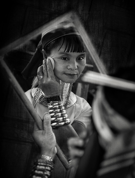 A woman from the Kayan tribe applying make up.   Kayah State, Myanmar 2017