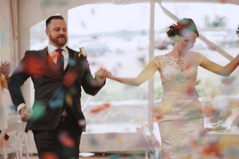 The bride and groom dance through confetti.