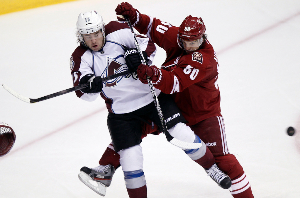 . Colorado Avalanche right winger P.A. Parenteau, left, is checked by Phoenix Coyotes center Antoine Vermette, right, away from a shot as Parenteau attempts to set a screen in front of the Coyotes\' net in the third period of NHL hockey game Saturday, April 6, 2013, in Glendale, Ariz. The Coyotes won 4-0. (AP Photo/Paul Connors)
