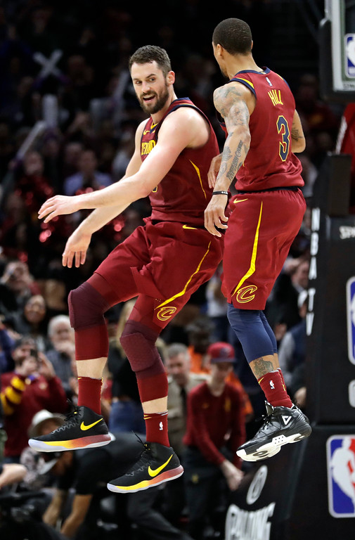. Cleveland Cavaliers\' Kevin Love, left, and George Hill celebrate after Love made a 3-point shot during the second half of the team\'s NBA basketball game against the Toronto Raptors, Wednesday, March 21, 2018, in Cleveland. The Cavaliers won 132-129. (AP Photo/Tony Dejak)